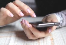 Woman Hands Texting On Smartphone In The Cafe_e5swmot6e__F0000